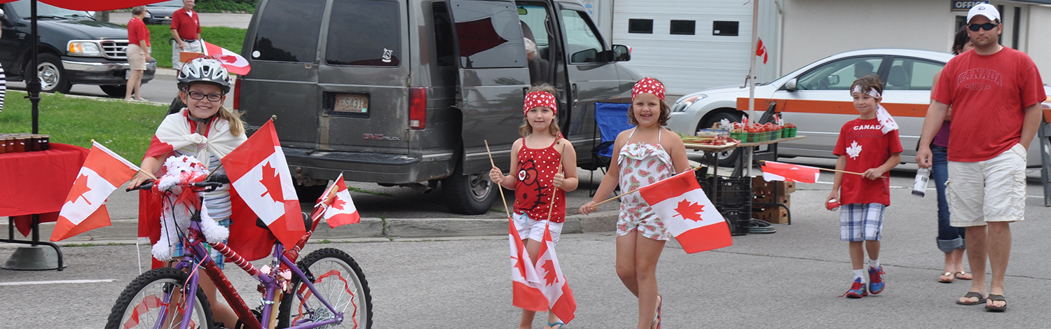 group of kids on Canada Day with decorated bikes and adults following